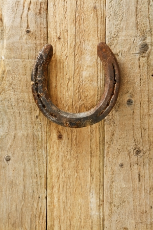 according: Old rustic horseshoe hanging on door said to bring good fortune and luck according to superstition