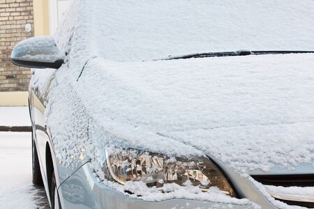 front bonnet and lights of european car covered in a layer of fresh snow during a harsh winter season