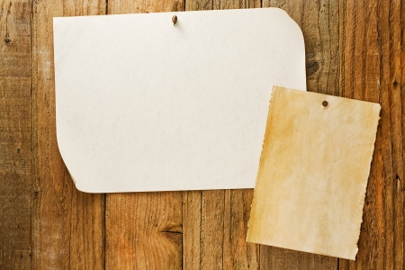 grungey: mottled beige parchment paper posters similar to the grungy cowboy wanted notices nailed to vintage wooden planks Stock Photo