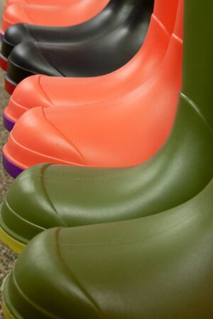 welly: Row of different colored rubber boots on a shelf in a retail outlet selling winter footwear