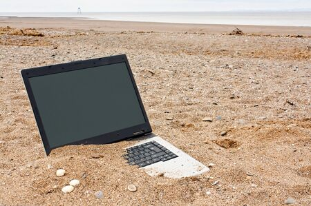 mishap: old or obsolete unwanted laptop on the beach with blank screen for your own message good concept for unwanted technology or travel websites Stock Photo