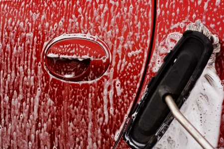 Washing the car with soapy soft brush at a car power wash photo