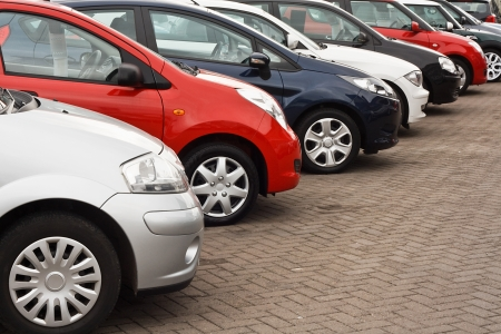 row of different european marques of used cars for retail sale on a motor dealers forecourt all logos removed Stock Photo