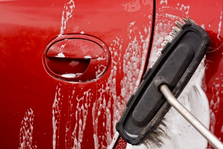 wash car: Washing the car with a soapy brush at a coin operated car jet wash
