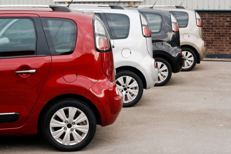 row of new cars for retail sale in a motor dealer yard showing same model in different color choices Standard-Bild