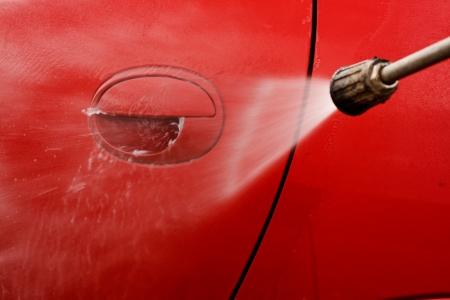 autolavaggio: Pulizia della macchina con una rondella di pressione a getto di lavaggio Archivio Fotografico