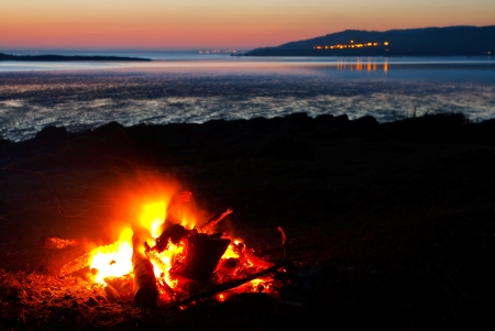 roaring sea: Roaring camp fire of real wood collected at the beach with the coast and sea in the vista Stock Photo