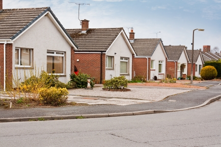 architecture detached house: row of modern suburban bungalows on a housing estate in suburbia Stock Photo