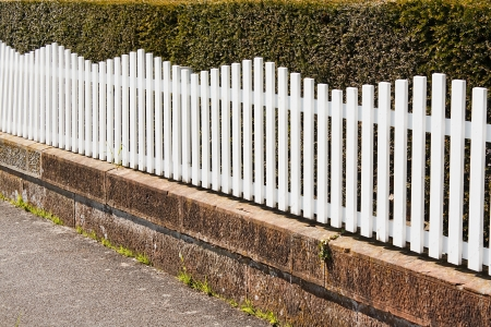 picket fence: White Picket fence next to pathway with bush behind Stock Photo