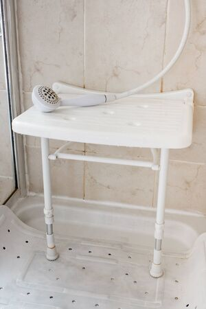 White Plastic shower seat used by the elderly and disabled to aid them by allowing them to sit and wash often reccommended by occupational therapists