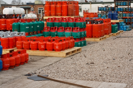 propane tank: Domestic propane gas bottles in storage at a distribution centre