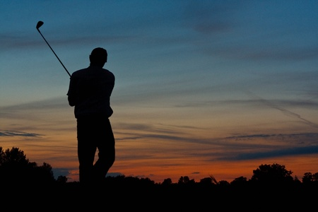Silhouette of a lone golfer finishing a game of golf at dusk photo