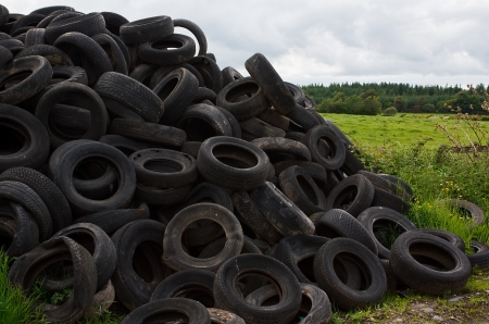 Pile of old vehicle tires dumped in the countryside by farmer Standard-Bild