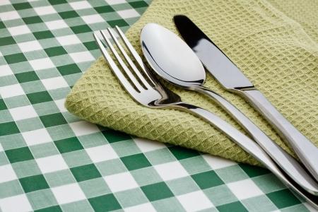 Serviette: cuchillo, tenedor y cuchara en una servilleta verde con un fondo de la guinga s�mbolo popular para los restaurantes Foto de archivo