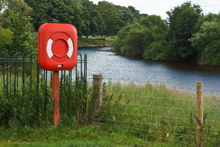 lifebelt: Red lifebelt beside a river in the country used as a floatation device for saving anyone who accidentally falls in the water to stop them drowning