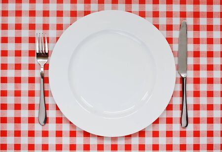Empty plate setting with plate, knife and fork on red gingham background popular symbol for diners and cafes photo