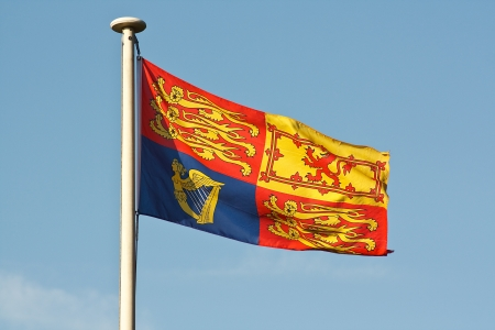 the sovereign: The Traditional Royal Standard Flag ripples in the wind on flagpole Stock Photo
