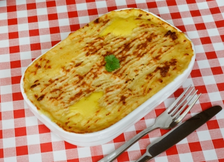potato cod: Traditional Homemade Fish Pie in a casserole dish with crispy mashed potato on the top on a red gingham tablecloth