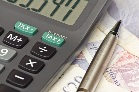 income tax: Calculator and pen symbolizing completing your personal Income tax returns for the inland revenue service or IRS