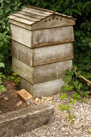 pollinate: Wooden beehive a home for bees who pollinate local trees and flowers whilst producing honey which is collected by the beekeeper Stock Photo