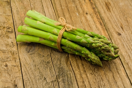 a bud  a sprout  a shoot: Asparagus bunch a premium seasonal vegetable on a rural rustic antique wooden table top setting Stock Photo