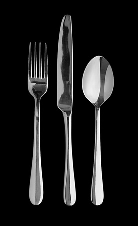 flatware: Silver table cutlery or flatware comprising of spoon, knife and fork isolated on a black background  Popular symbol for diners, cafes and good food competitions and food festivals Stock Photo