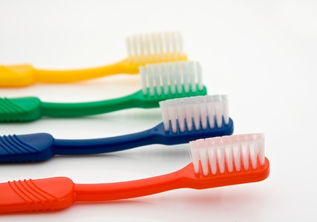 Detail of a row of different colored toothbrushes with the front one in selective focus good for dentists photo