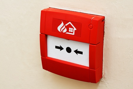extinguisher: wall mounted Red fire alarm button used to activate warning systems in buildings