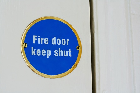 Sign telling people to keep an entrance shut to stop a blaze spreading around a house by being stopped at the fire door photo