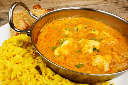 tandoori chicken: Chicken Korma a popular sweet indian curry dish of coconut and cream sauce served in a dish on a plate with pilaf rice and samosas
