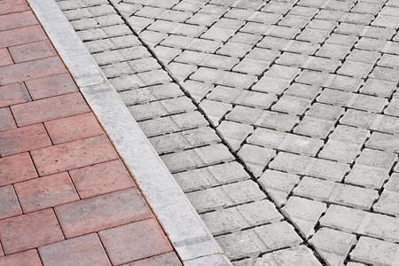 concrete surface finishing: Brick paving types with pink sidewalk, curb and drive made from plain interlocking concrete bricks Stock Photo