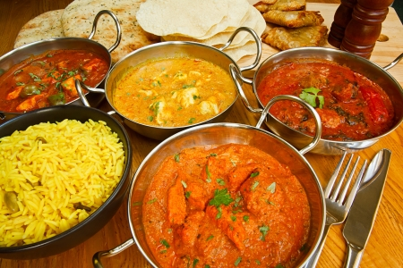 Selection of indian food with pilau rice, naan bread, poppadoms and samosas a popular choice for eating out in european countries photo