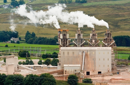 greenhouse effect: Four industrial chimneys belching smoke into the atmosphere