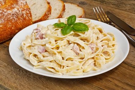 Plate of tagliatelli carbonara italian food in a rustic restaurant setting