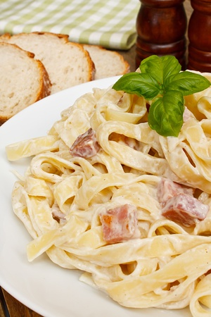 bacon bits: close up of a plate of tagliatelli carbanara italian cuisine in a traditional restaurant setting