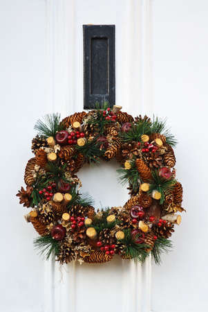 Festive Christmas wreath on white door at xmas photo