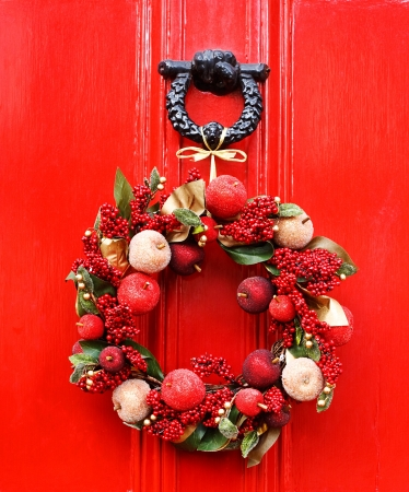 decorative Christmas wreath tied to knocker on red door