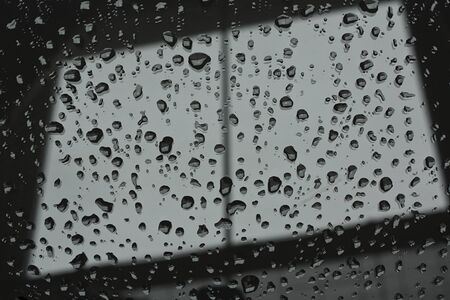 glazing: Abstract photograph of a window pane with raindrops on symbolising dull wintry weather