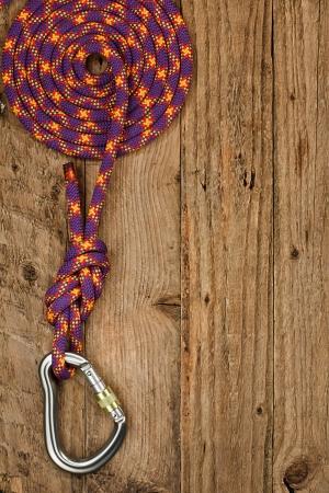 Kletterausrüstung mit Seil und Verbinder auf rustikalen hölzernen Hintergrund oft Sicherungsgerät oder Abseilen von Bergsteigern genutzt Standard-Bild