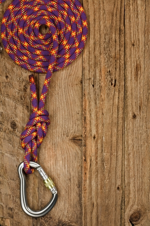 recreational climbing: Rock climbing gear with rope and connector on rustic wooden background often used for belay or abseiling by mountaineers Stock Photo