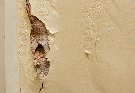 crack house: Damaged plaster wall in need of renovation by painters and decorators inside a residential home Stock Photo