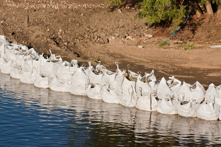 sandbag: Row of large industrial sandbags holding back a river and protecting against flooding Stock Photo