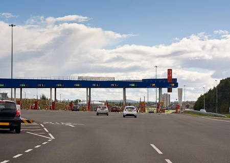 toll: Cars approaching a toll gate, erected to charge drivers for the use of a road and fund maintenance, repair and new transport projects  Stock Photo