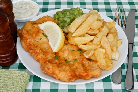 haddock: Plate of fish and chips with mushy peas and a slice of lemon on a diner table  A traditional British Seaside Dish