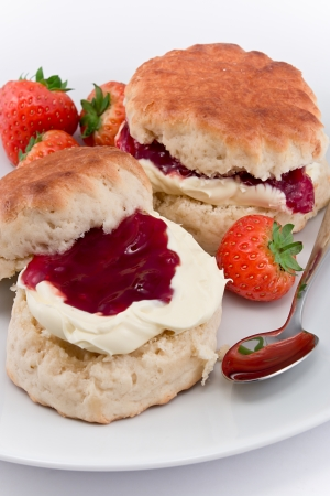 cream tea: Traditional Afternoon Tea of Devonshire scones topped with clotted cream and strawberry jam often served with coffee or tea Stock Photo