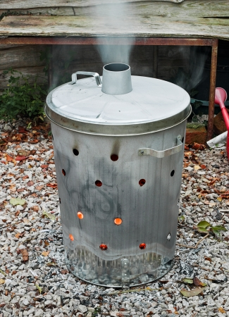 incinerator: Garden incinerator bin burning garden waste with smoke coming out of the flue Stock Photo