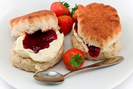 scones: Traditional Afternoon Tea of Devonshire scones topped with clotted cream and strawberry jam often served with coffee or tea Stock Photo