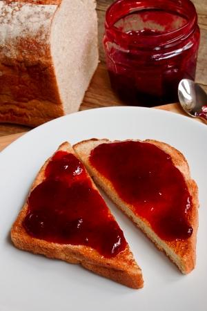 mixed fruit jam on toast isolated against a white background photo
