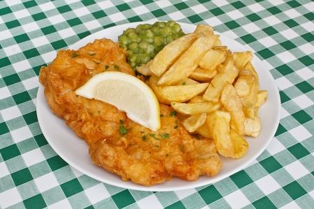 fish and chips: Primer plano de pescado y papas fritas con guarnición de puré de guisantes y una rodaja de limón, en una tradicional mesa Diner Foto de archivo