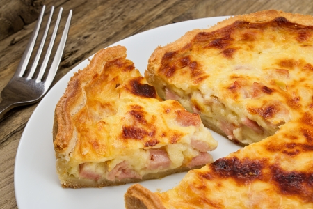 Portion of cheese and bacon flan cut from the quiche lorraine in a rustic traditional farmhouse setting
